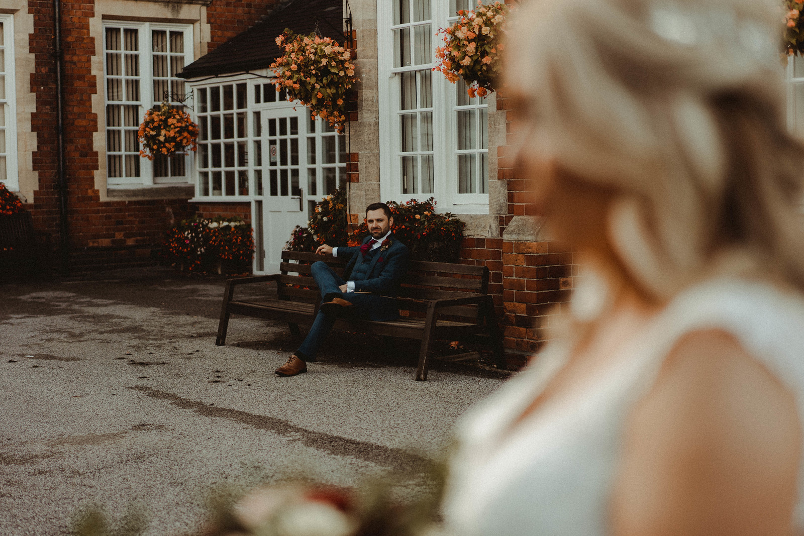 groom looks over the bride, as the bride cuts into the camera shot. Autumn wedding