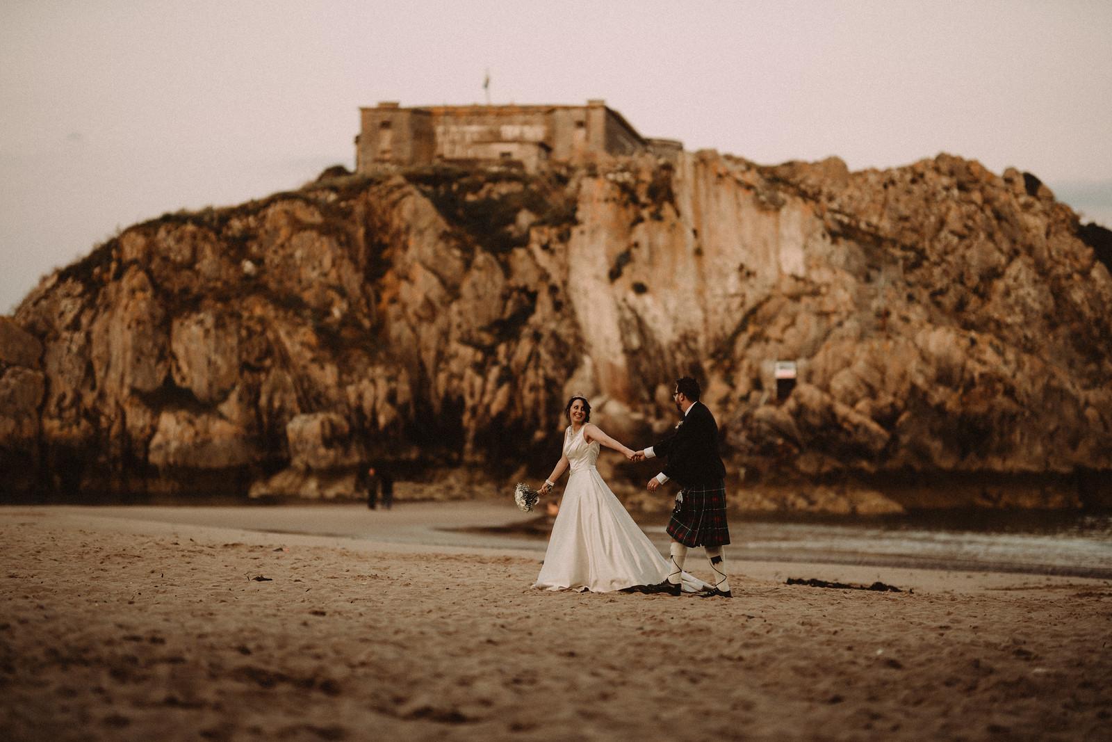 Bride and groom walking across the beach in Tenby