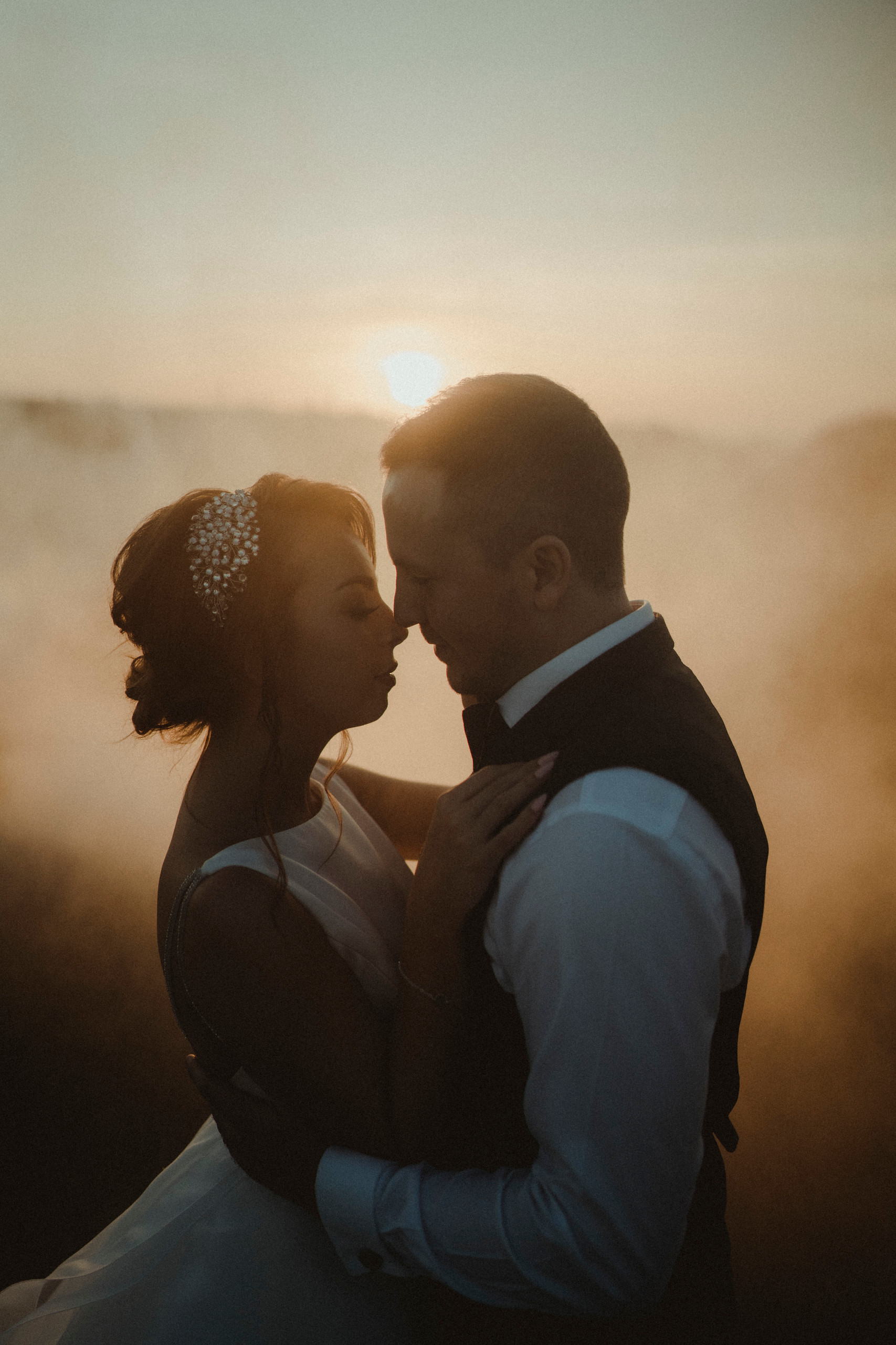 Bride and groom hold each other close as the sun is setting behind them