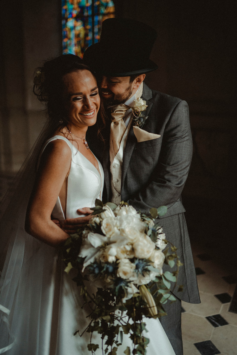Groom leans his head on the brides face as they both smile