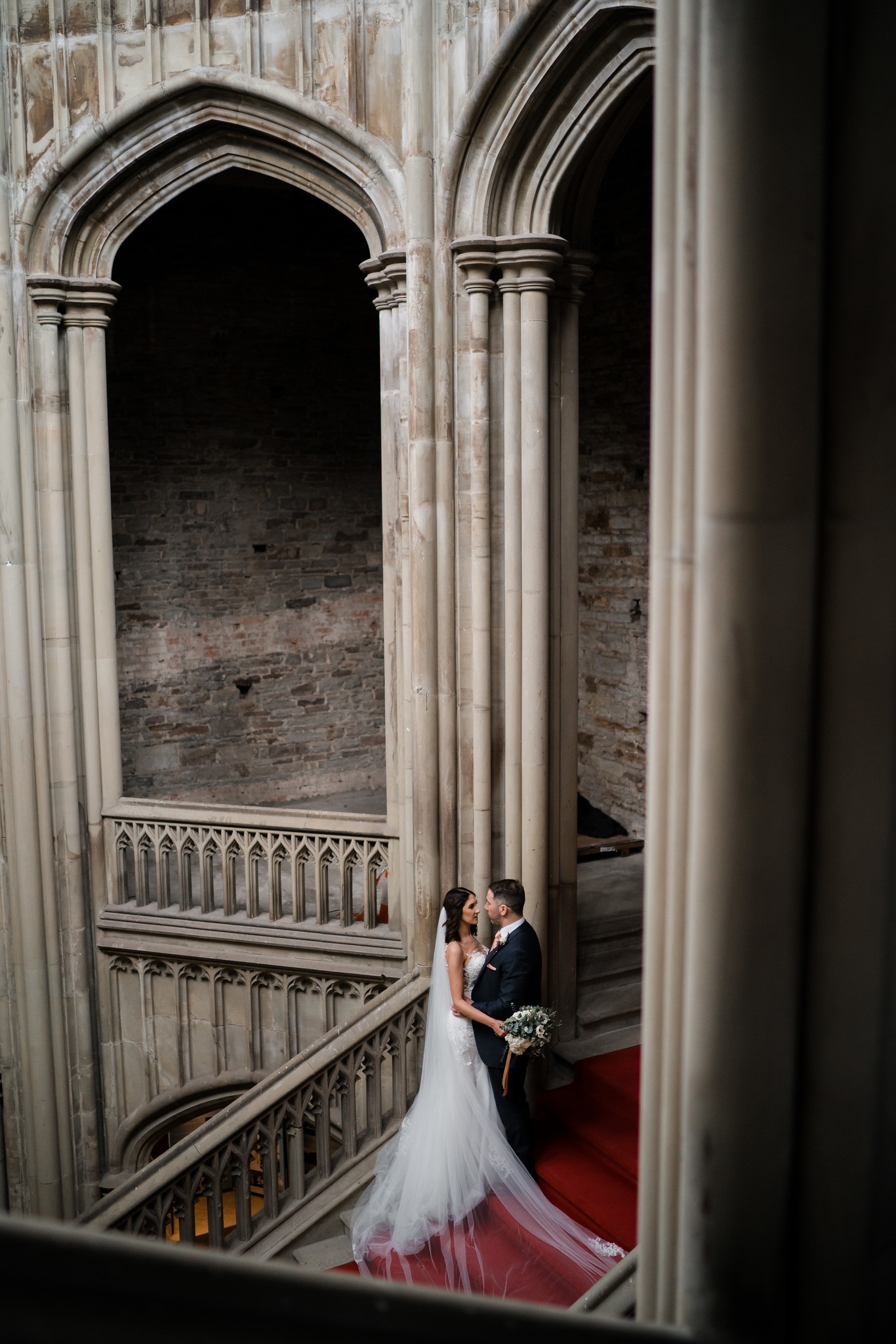 Bride and groom look at each other standing on top of the grand stairs