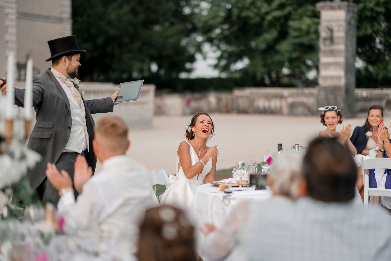 Bride is laughing a lot as the groom finishes his wedding speech
