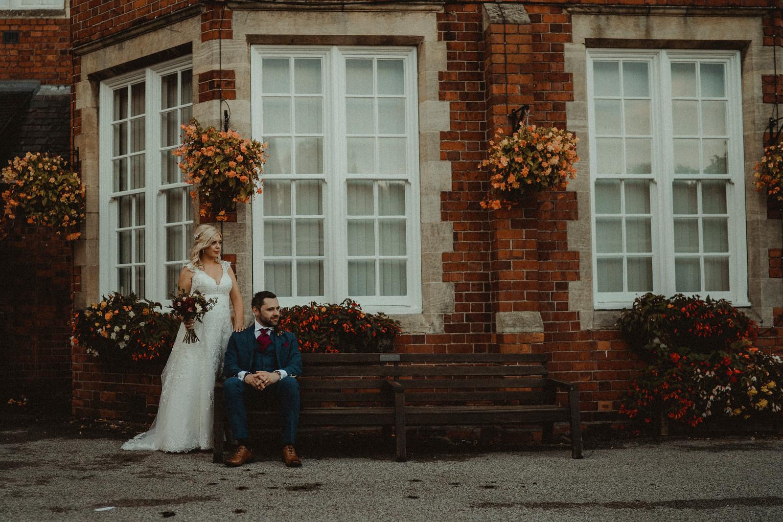 Bride and groom sat outside their wedding venue  Autumn wedding