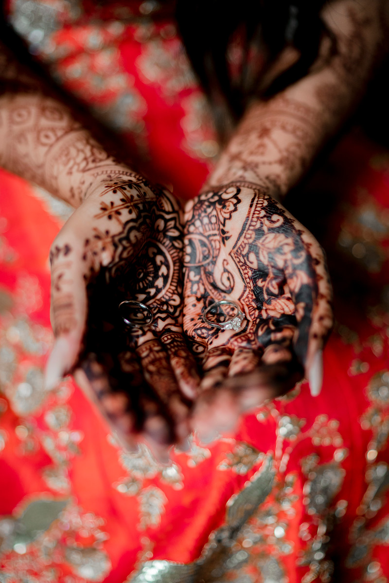Close up of the brides hands covered in henna with the brides and grooms rings