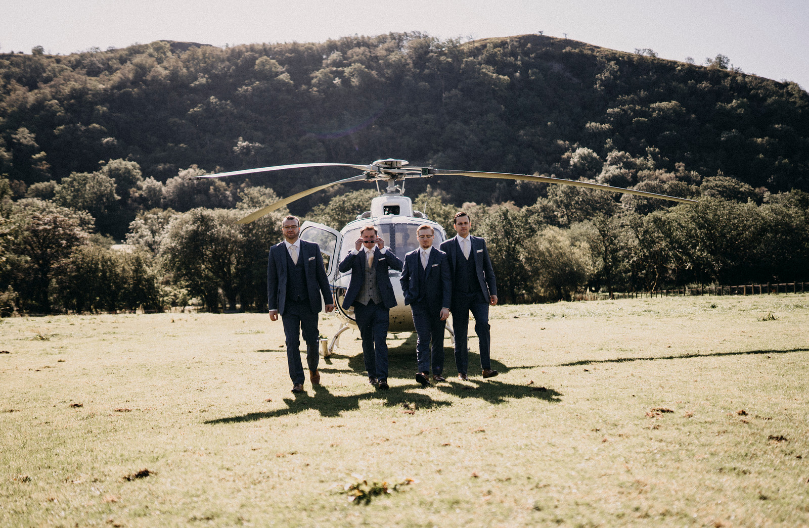 Groomsmen walk away from a helicopter