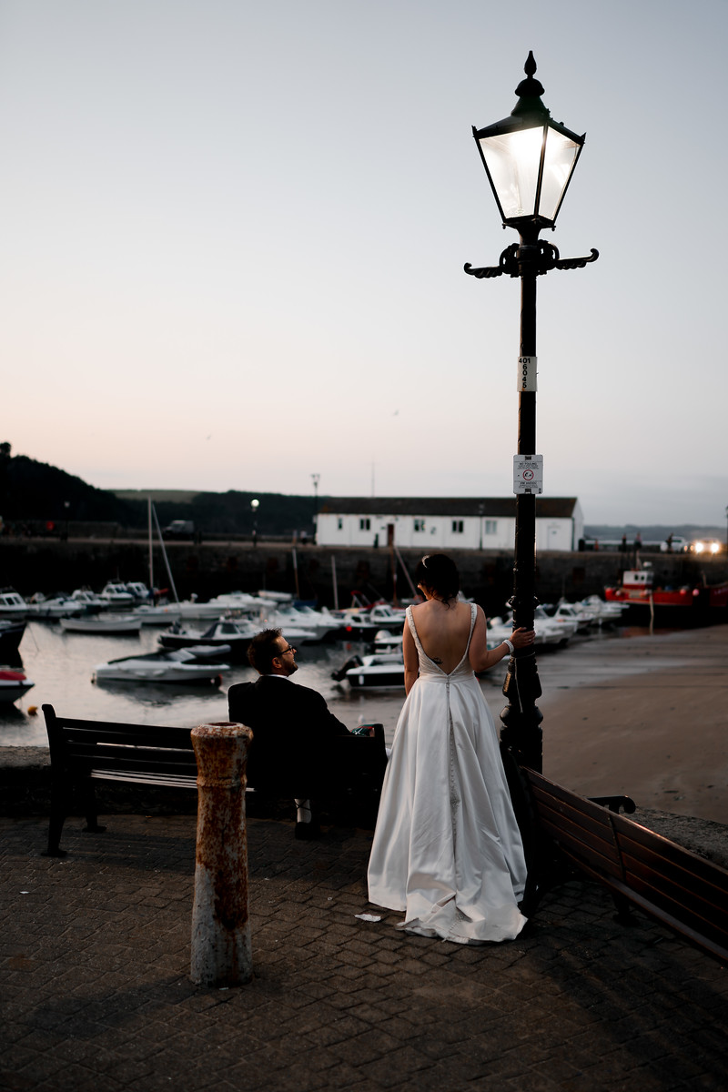 Bride and groom look over the harbour in Tenby| Fun beach wedding