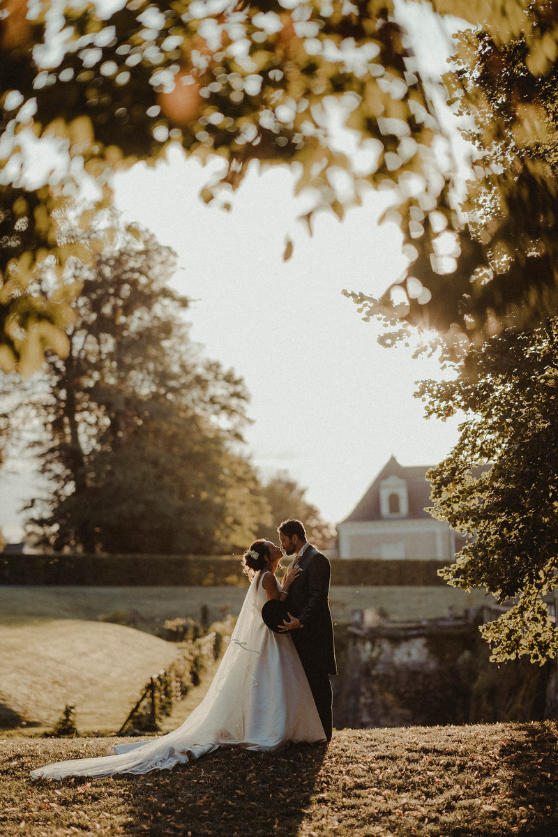 Bride and groom kiss outside in the beauty of their venue