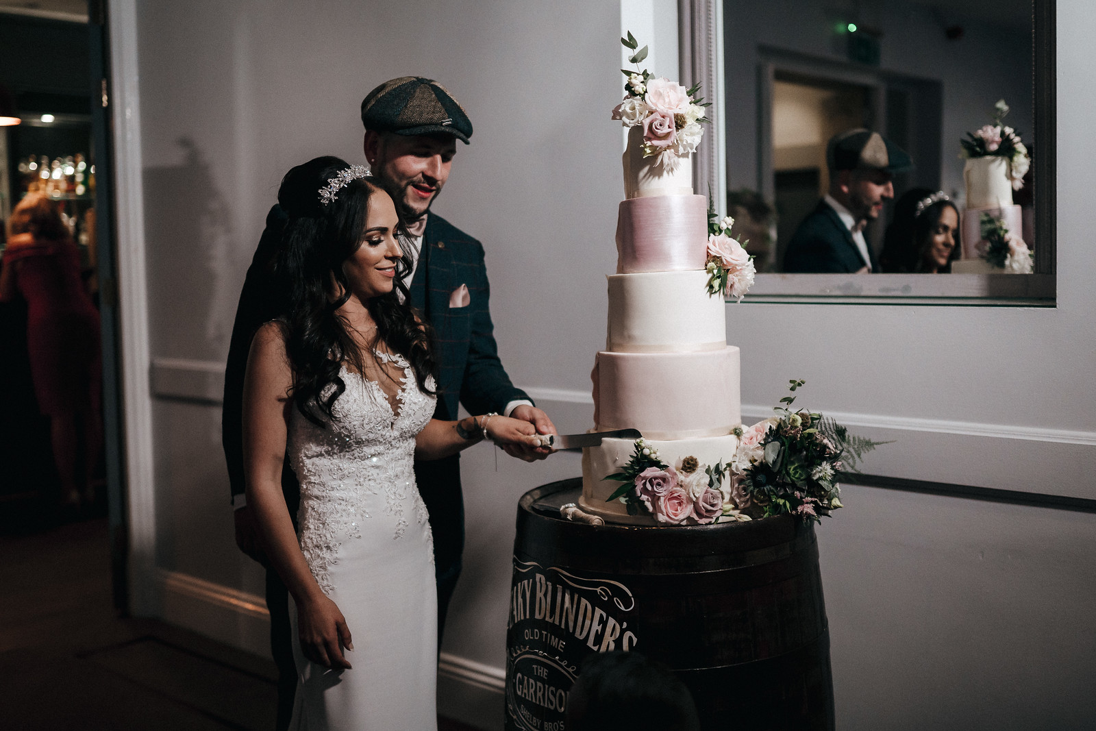 Bride and groom smiling as they cut their cake