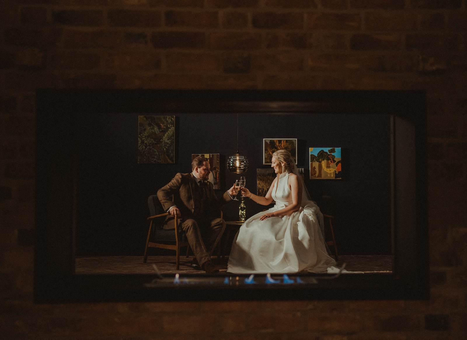 A bride and groom cheers and celebrate as they are pictured through a glass window in the fireplace| Unique wedding venue