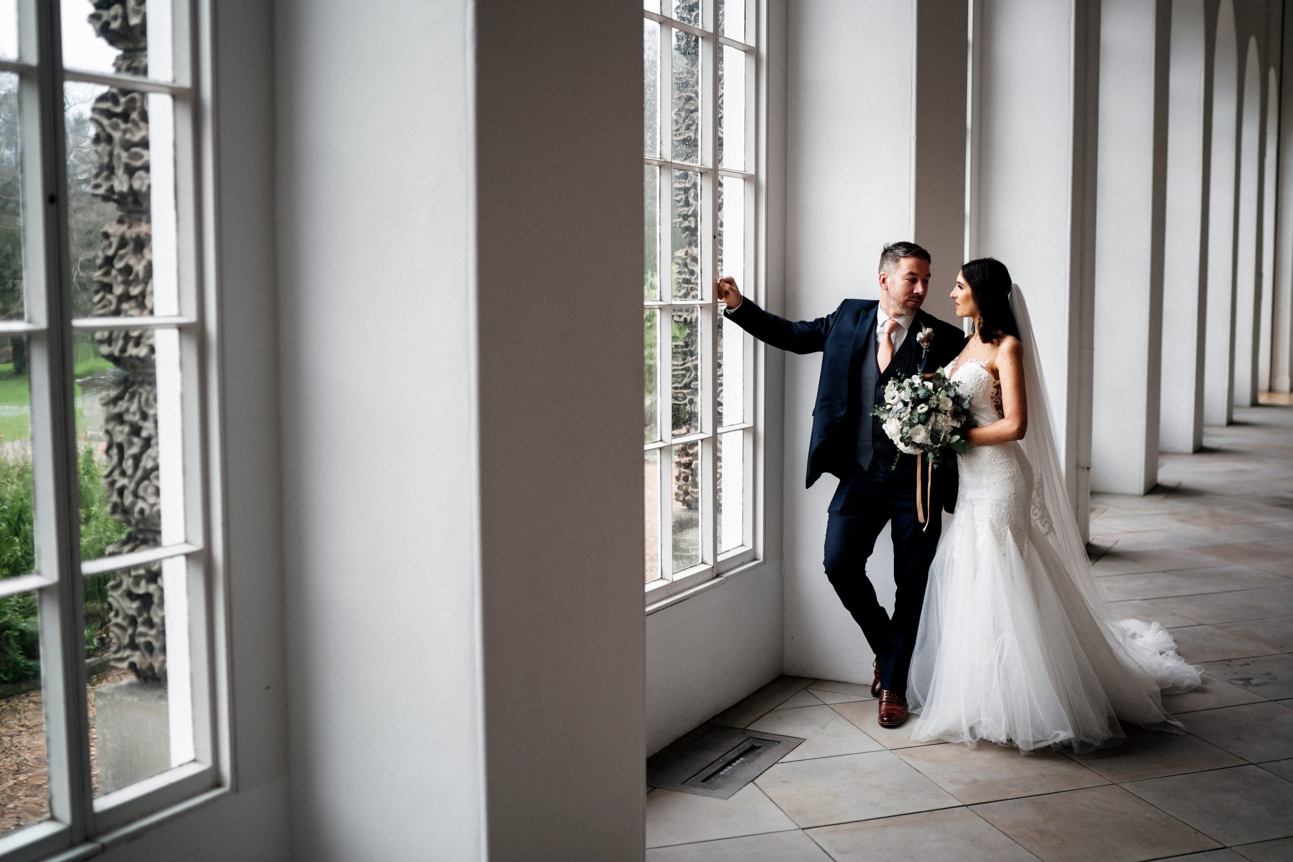 Bride and groom stand next to a giant window| Perfect day for the bride and groom