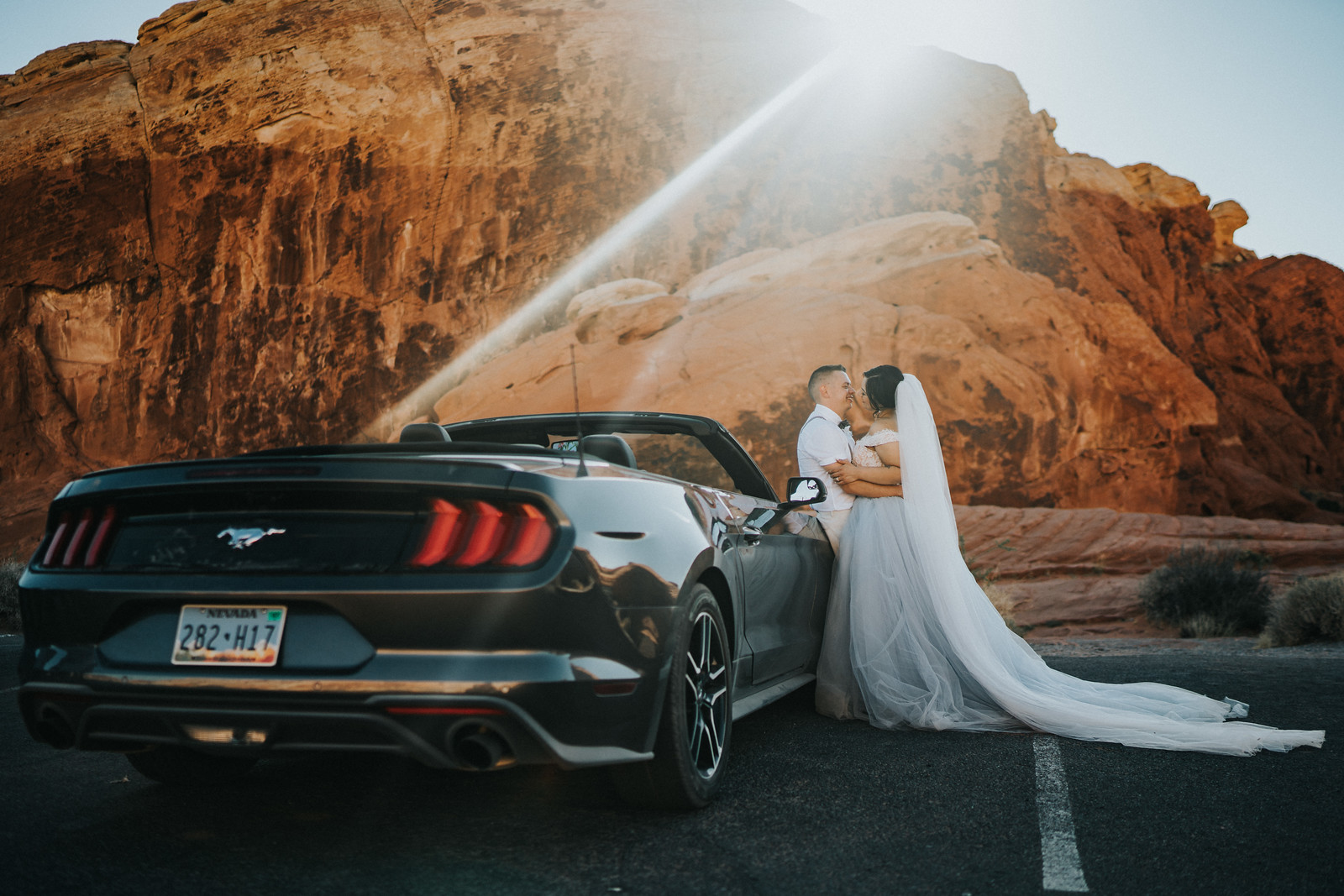 The couple look at each other whilst standing next to a car and their rock formation wedding venue in the background