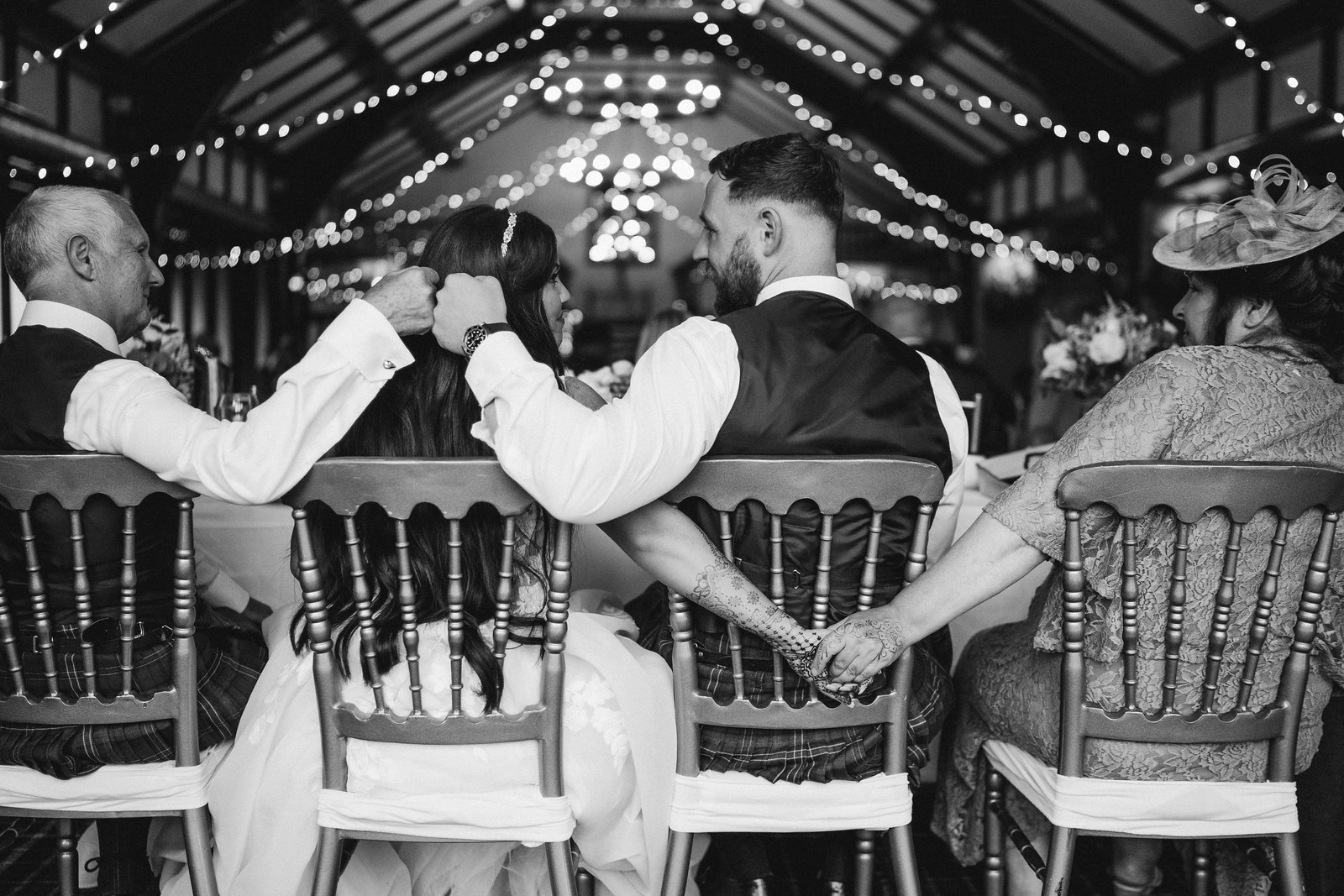 A unique family photo, the bride and groom look at each other, the bride holds hands with her mother and the groom fist pumps with the brides father