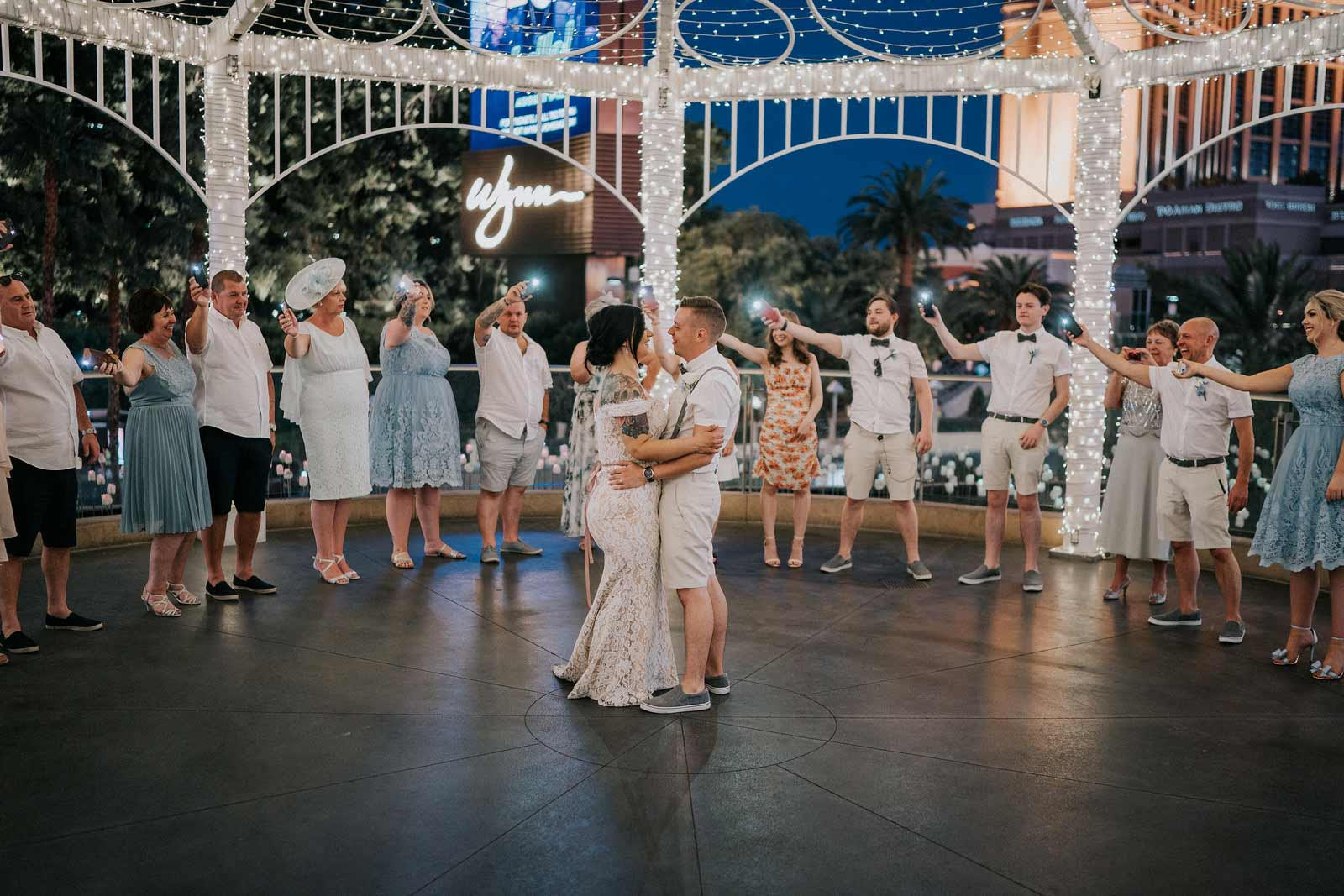 Bride and groom have their first dance around their family and friends as they hold their phones with the lights on