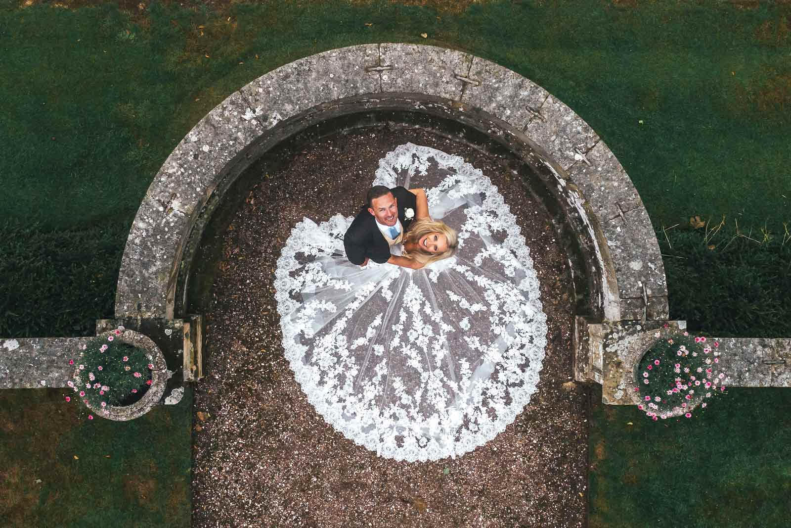 Bride and groom look up, as the drone takes the photo. The brides lace train covers where the couple is standing