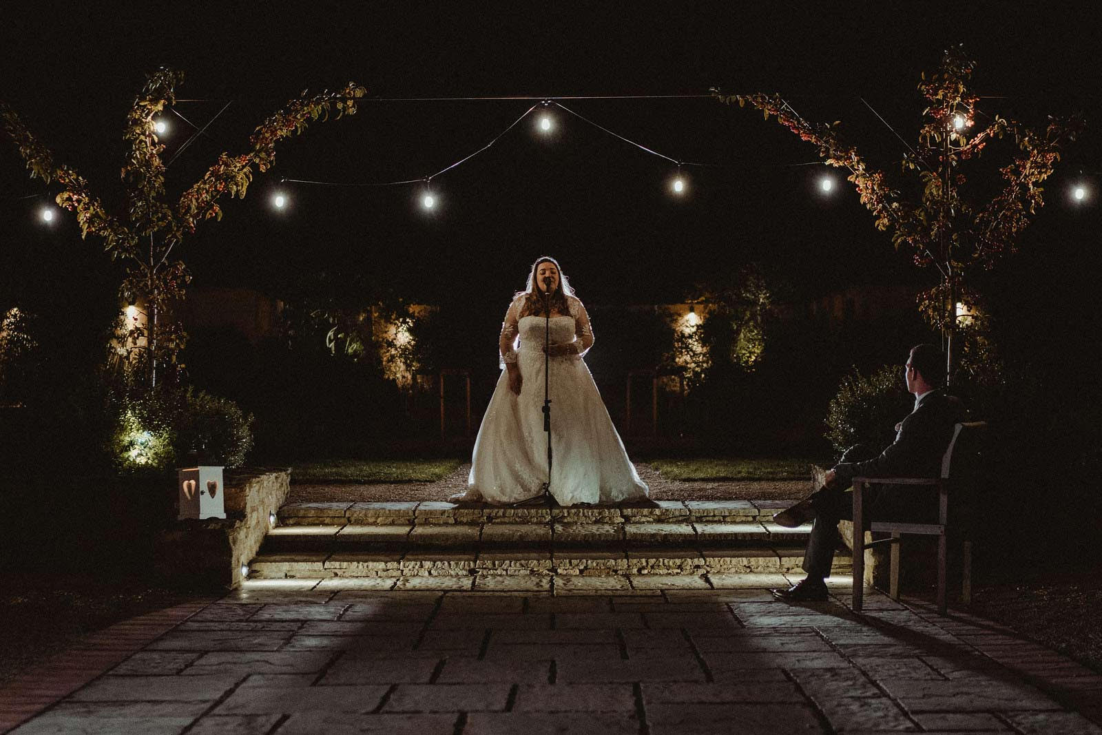 Bride singing as her groom watches on| Cotswold Wedding Venue