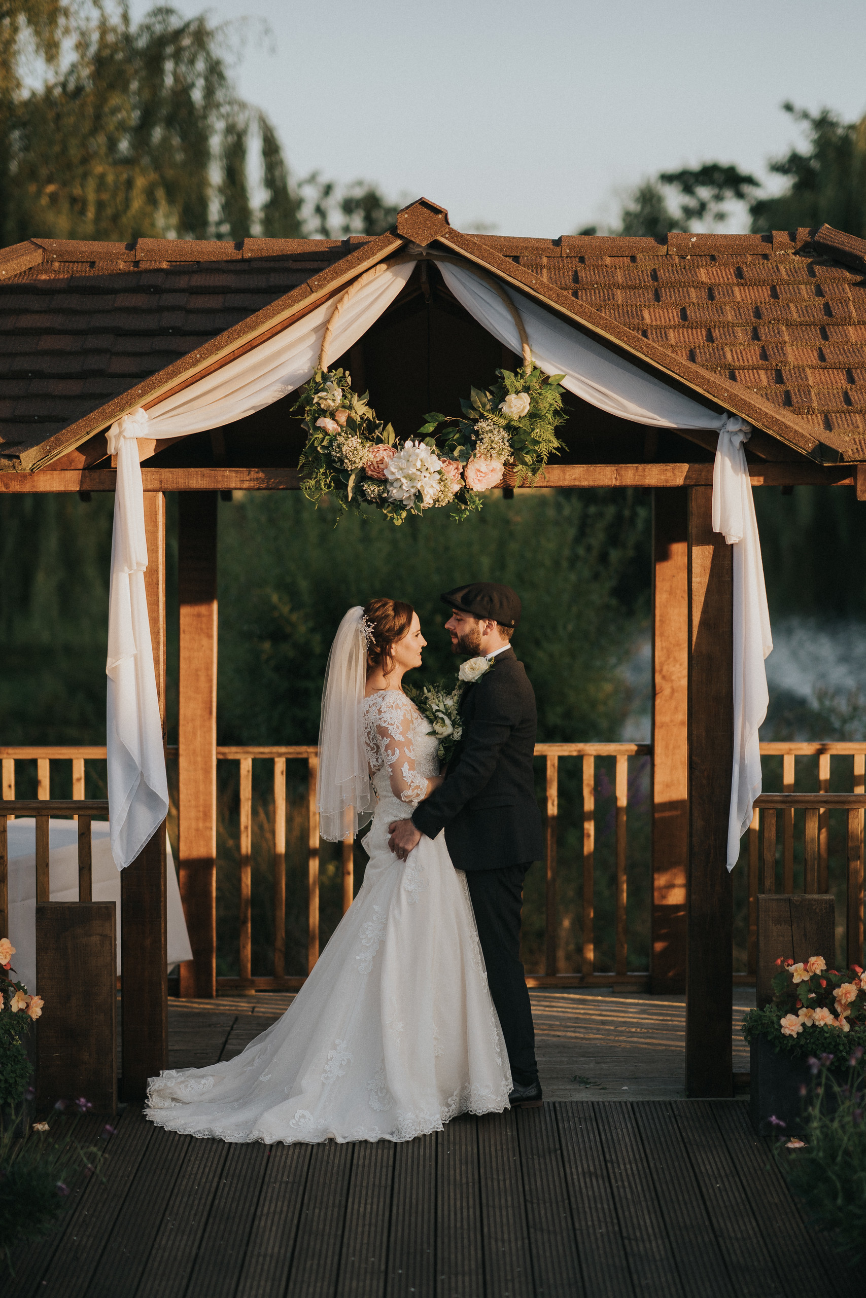 Bride and groom stand by their outside wedding looking at each other