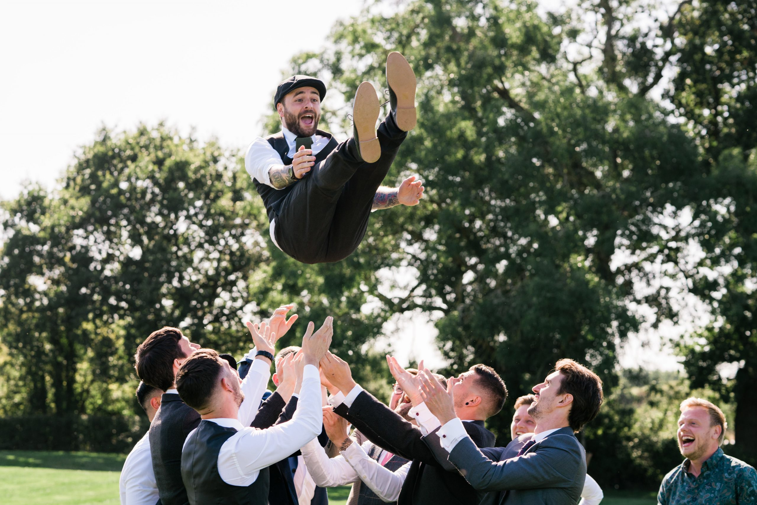 Groom is thrown in the air by his groomsmen as they are all laughing and smiling