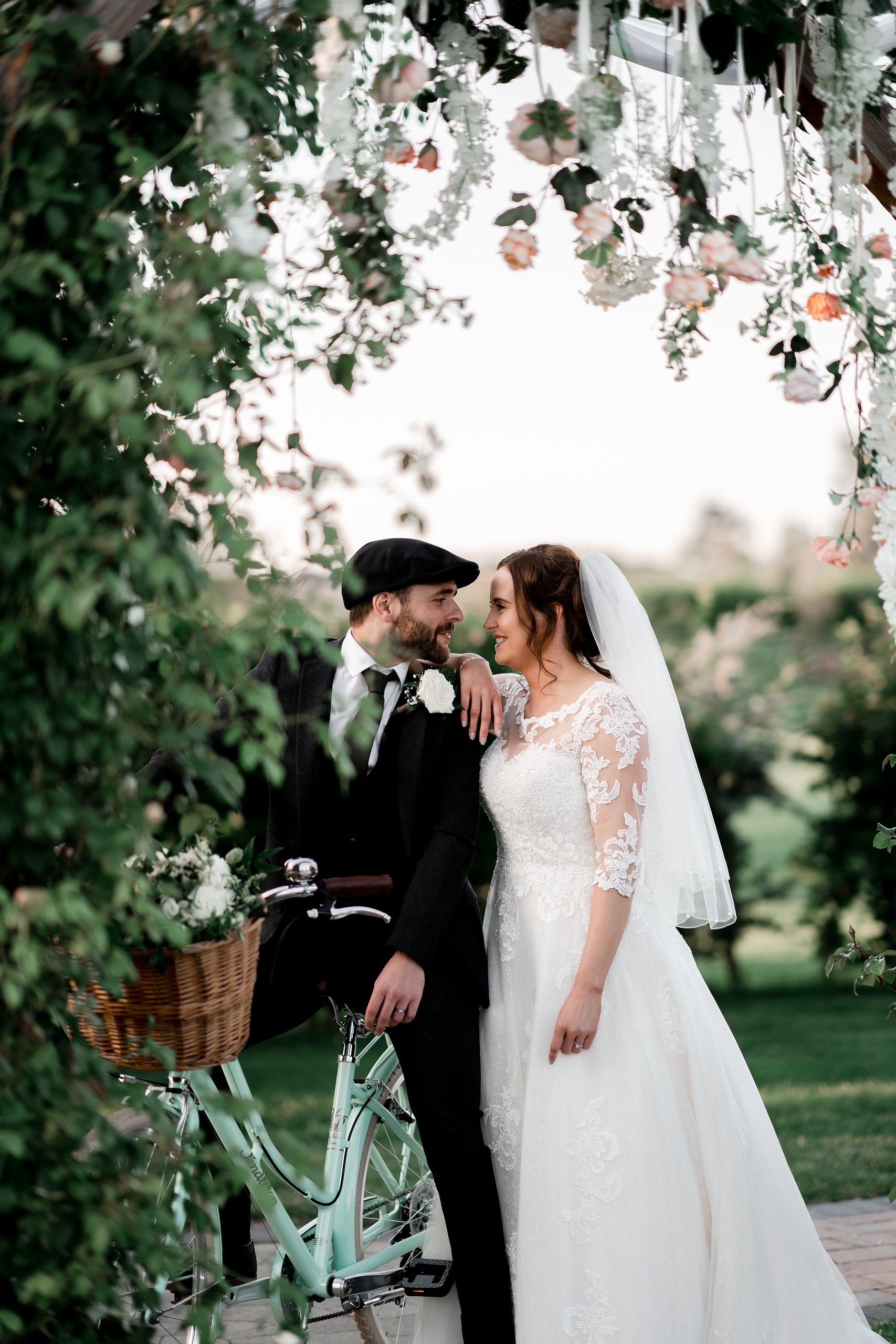 Bride and groom look into each others eyes, groom on a traditional bike and greenery all around