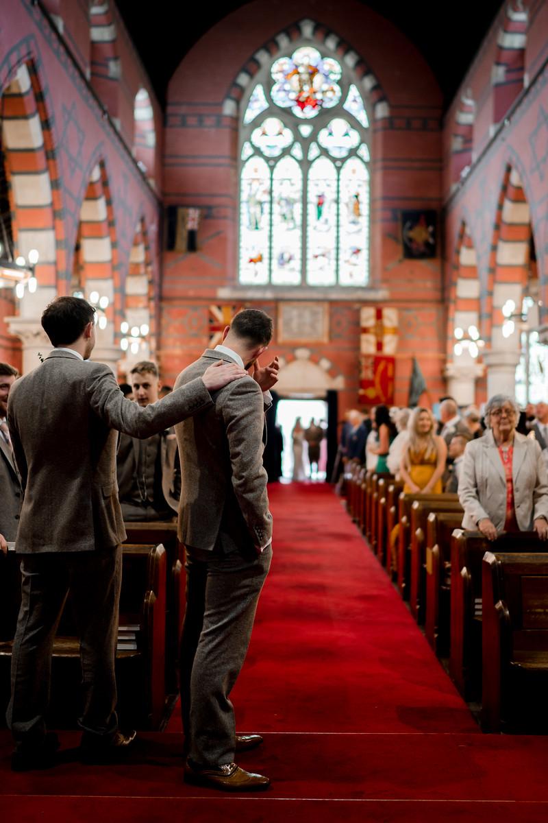 Groom wipes away tears as his bride walks down the aisle