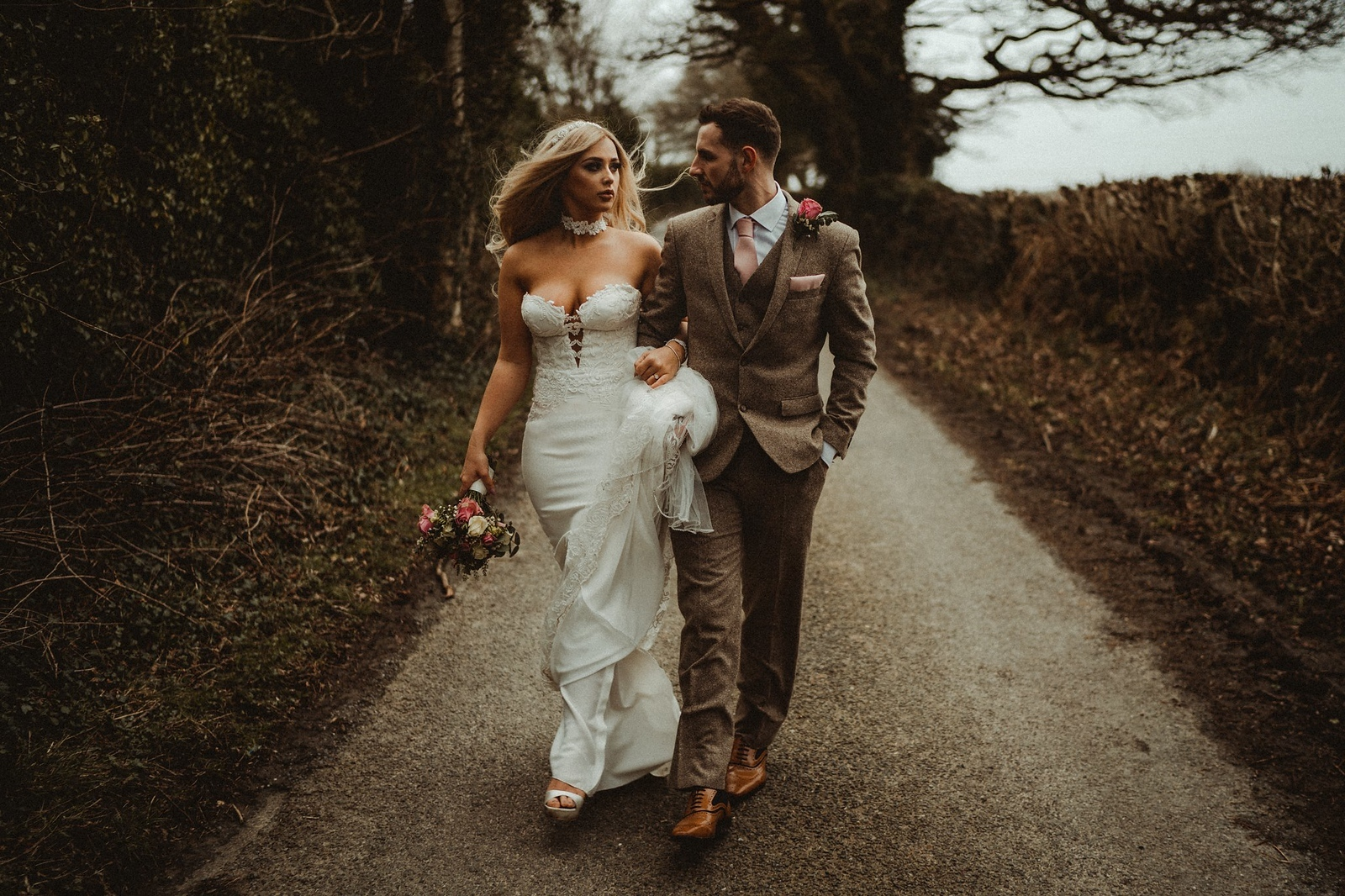 Bride and groom look at each other whilst walking down a country lane
