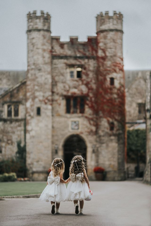 Two young children walk towards the wedding venue