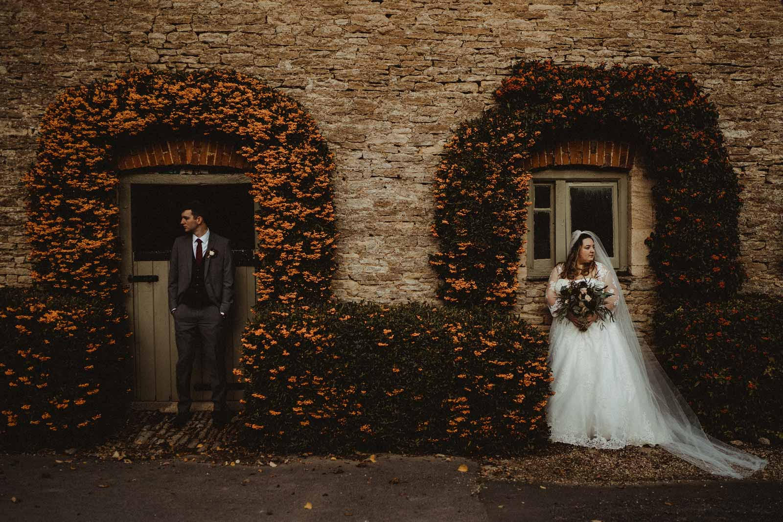 Bride and Groom standing in the archway of windows| Cotswold Wedding Venue