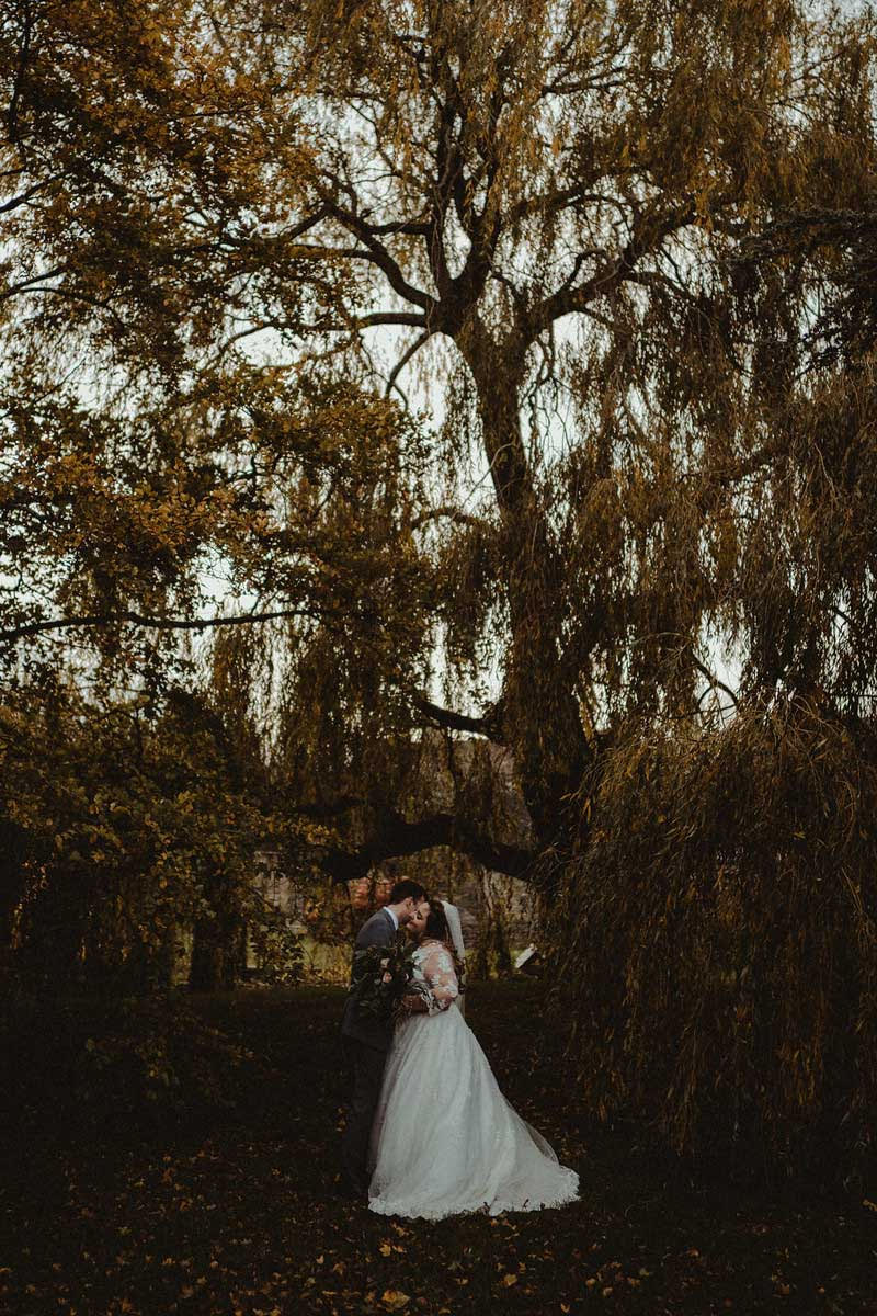 Bride and groom kiss under the gorgeous greenery of their wedding venue| Cotswold Wedding Venue