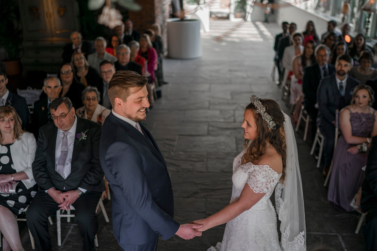 Bride and groom hold hands and smile, as family watch them get married - wedding photographers Northumberland