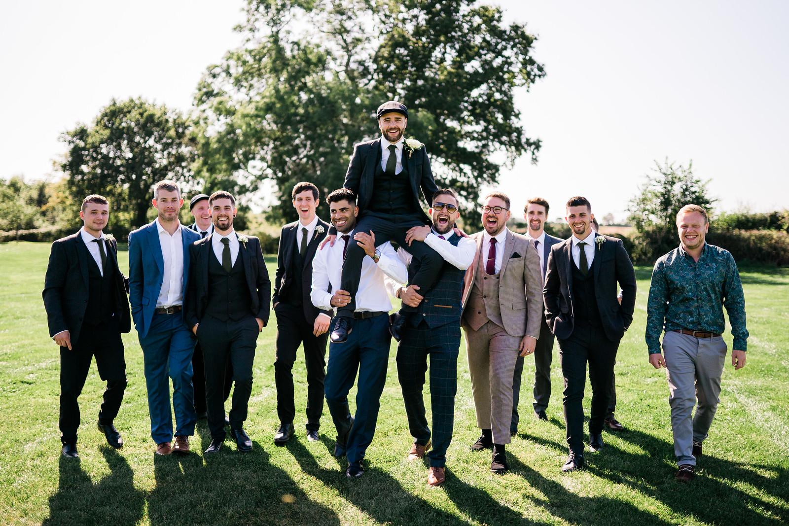 Groomsmen carry the groom on their shoulders