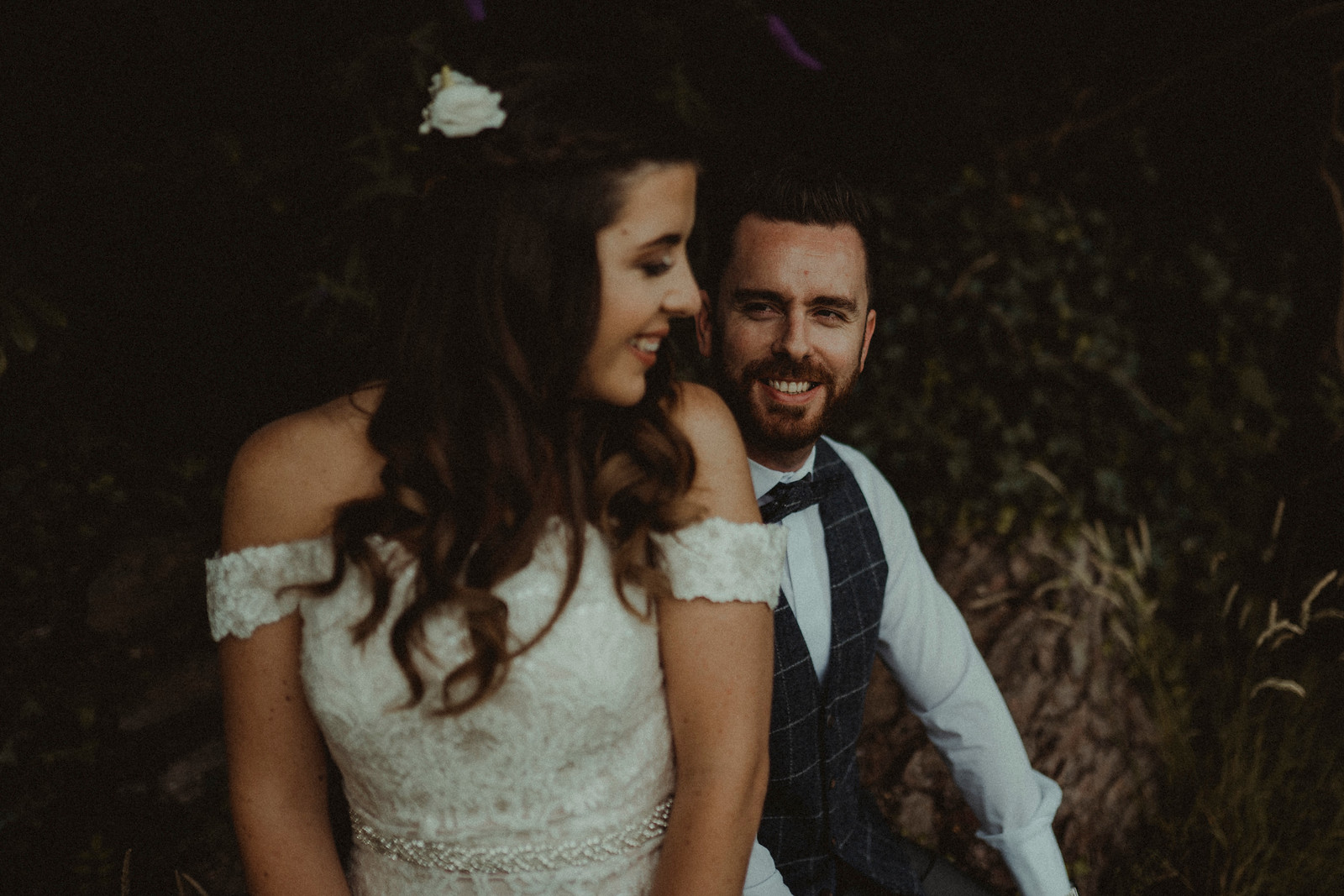 Bride and groom smiles at each other in their outdoor wedding