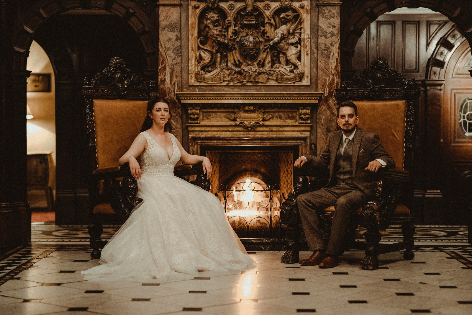 Bride and groom say in grand chairs| Wedding photographers