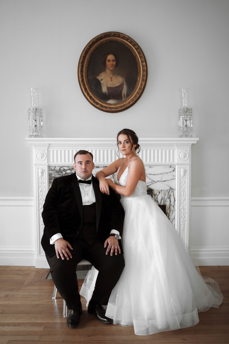 Bride and groom looking directly at the camera, groom is sat down and the bride is lent on the grooms shoulder