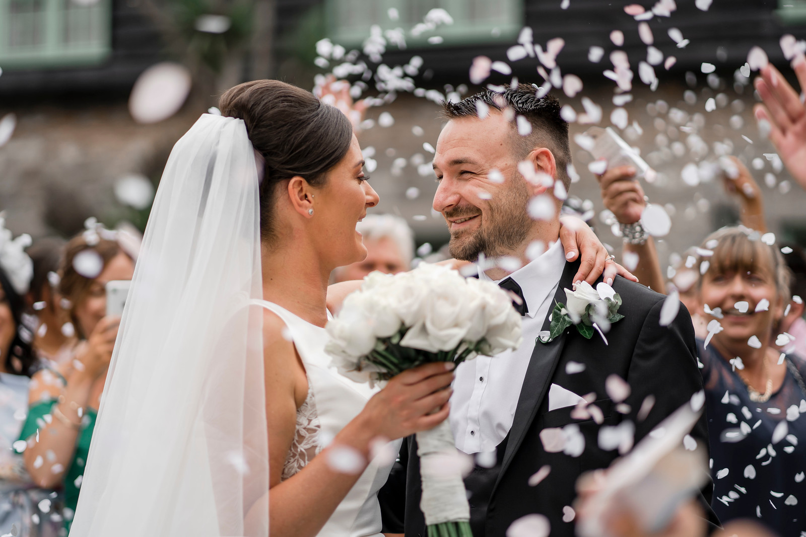Bride and look smile at each other as loved ones throw confetti over them| Wedding photographer and videographer
