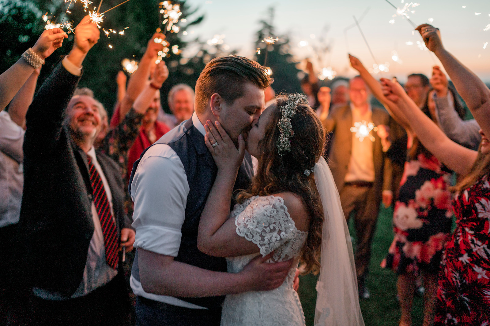 Bride and groom kiss as family and friends hold sparklers around them - wedding photographers Northumberland