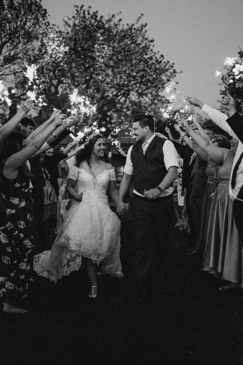 Bride and groom smile as family and friends hold sparklers around them - wedding photography Northumberland