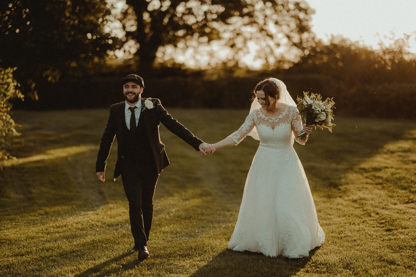 Bride and groom hold each others hands as they walk through the beauty of the venue