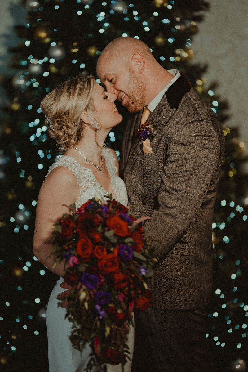 Bride and Groom kiss by a ChristmasTree| Wedding Photos