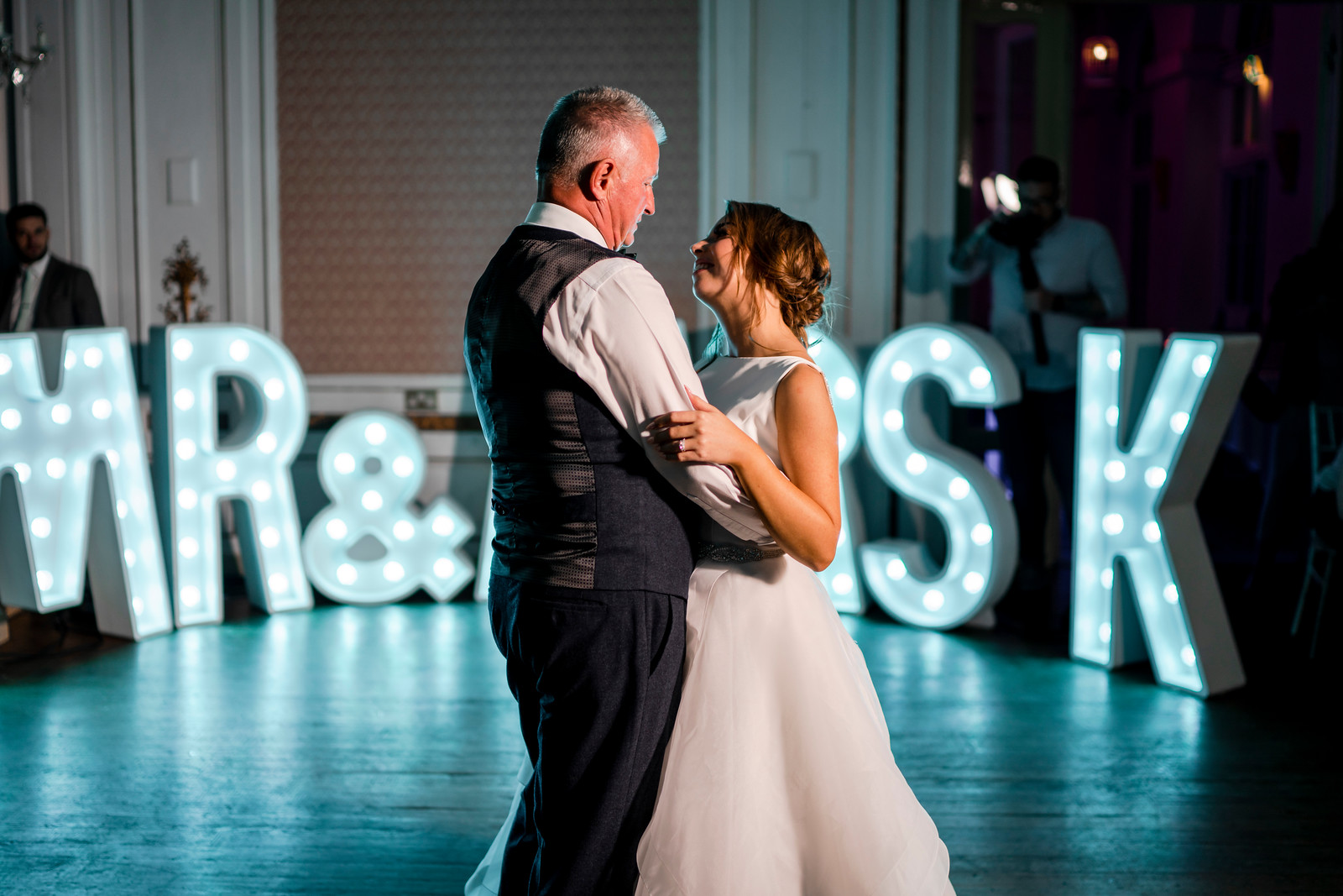 Father and bride look at each other as they dance together