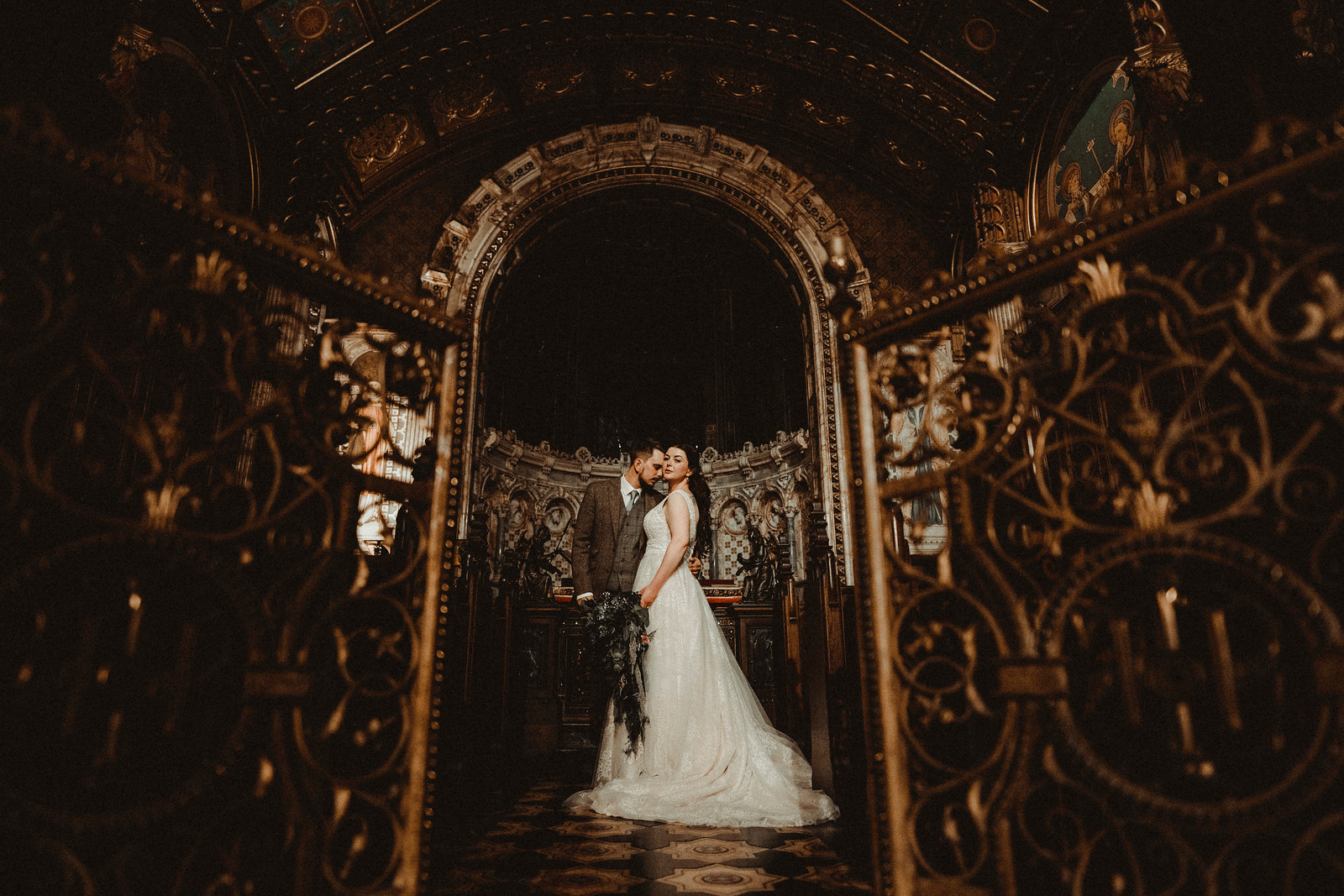 Bride and groom stand in the archway of their venue| Wedding photographers