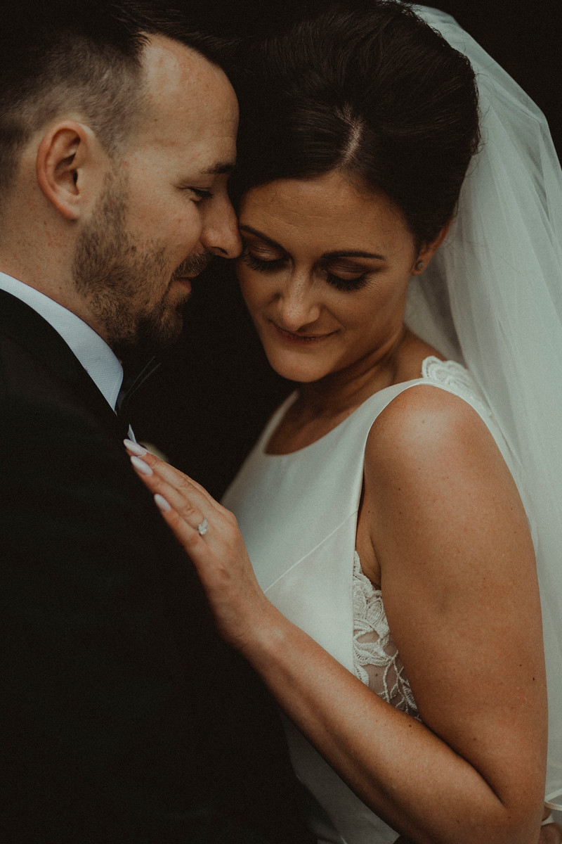 Bride and groom lean their heads against each other