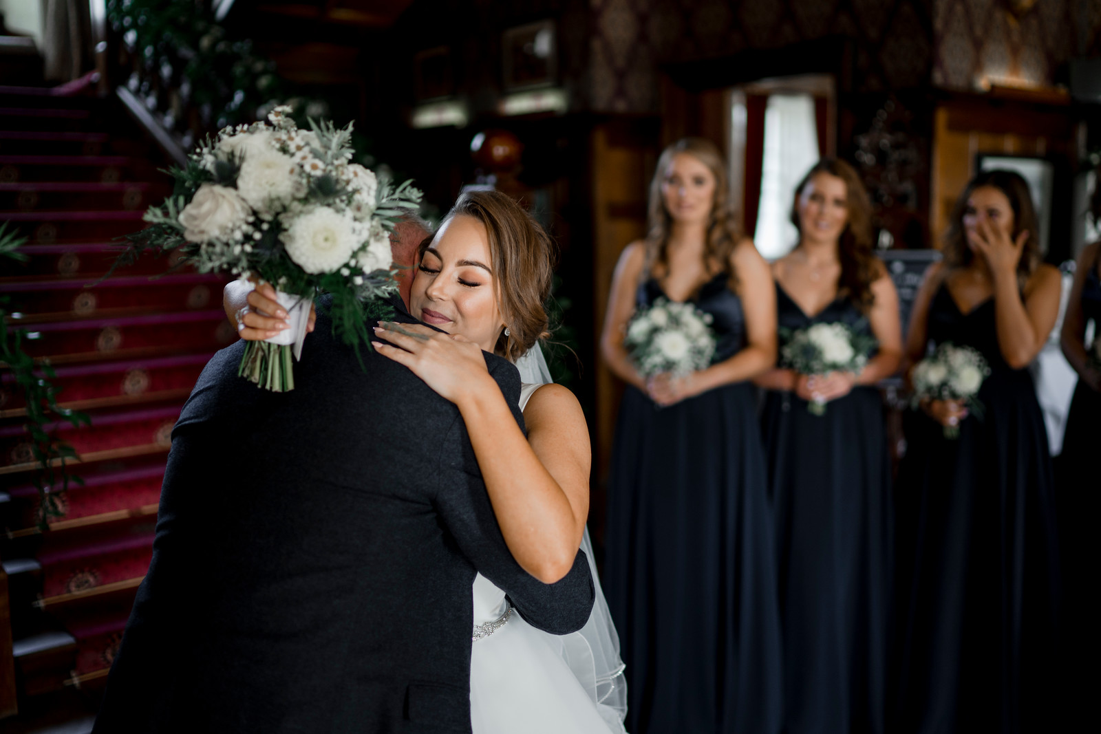 Bride and her father hug as the bridesmaids tear up in the background