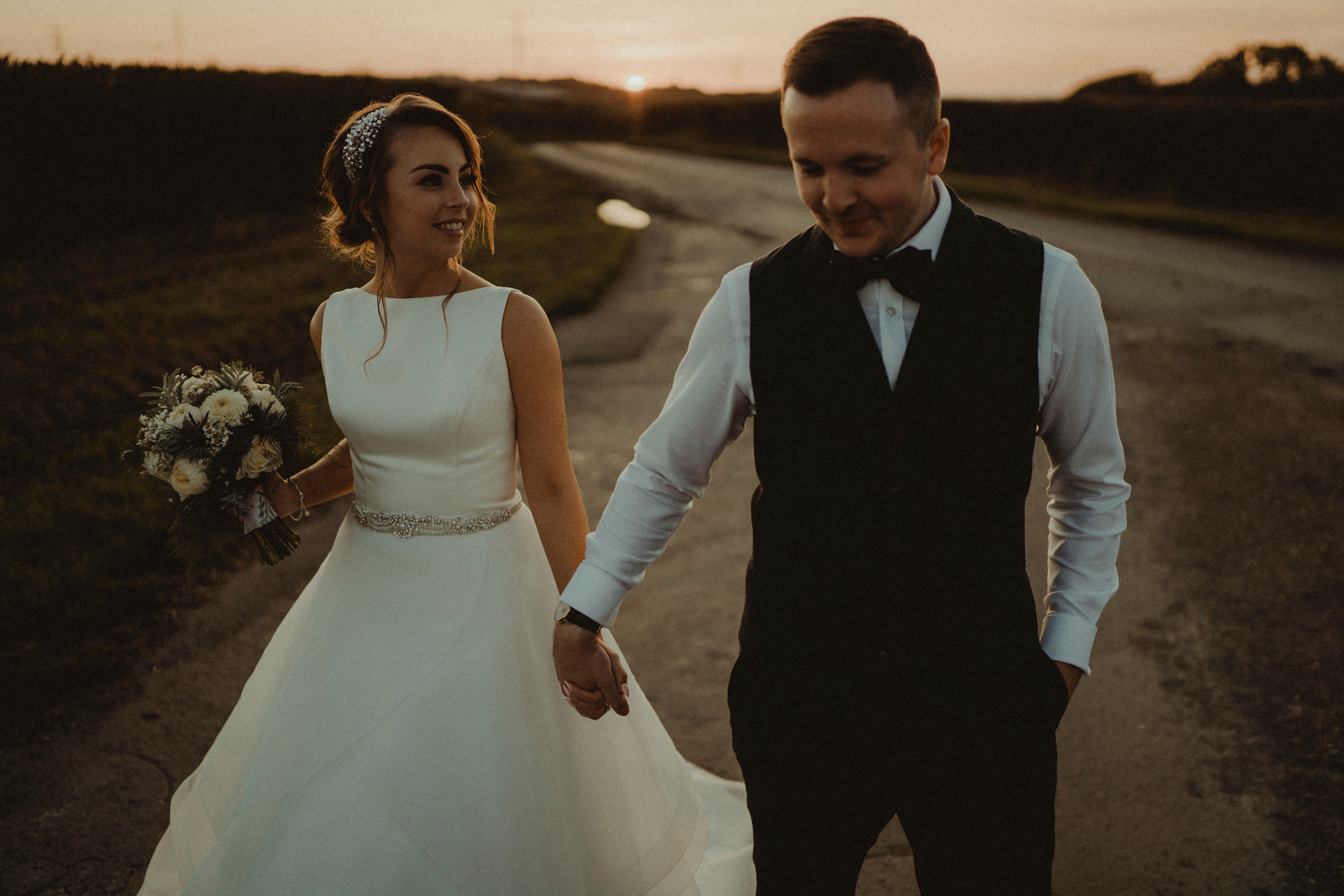 Bride and groom hold hands as they walk down the country road