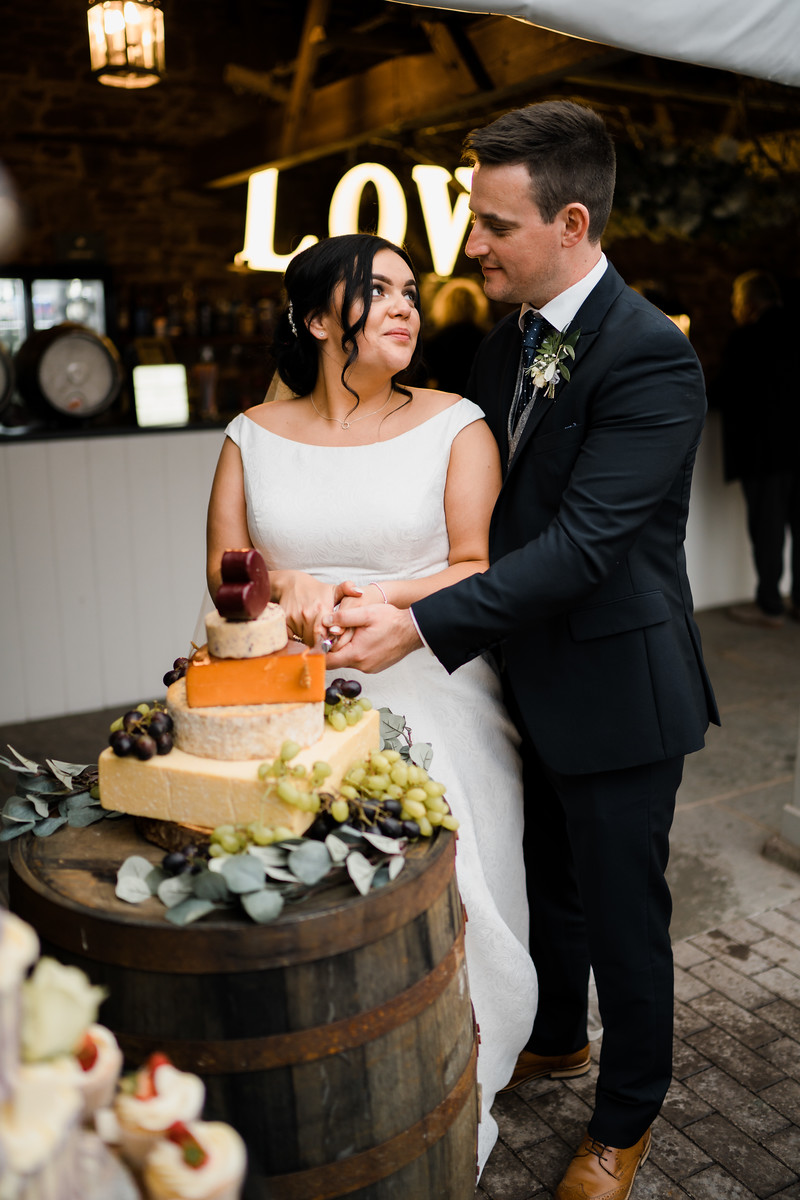 Bride and groom cutting their unique cheese wedding cake - South Wales wedding photographers