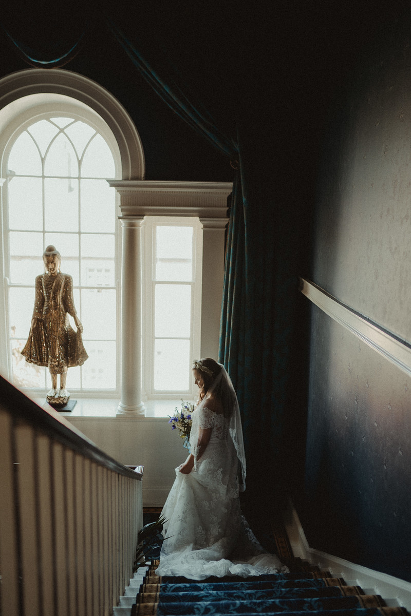 Bride walks down the grand staircase - wedding photographers Northumberland