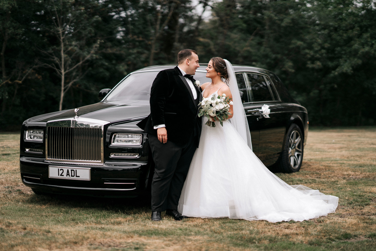 Bride and Groom smile at each other as their wedding car is behind them