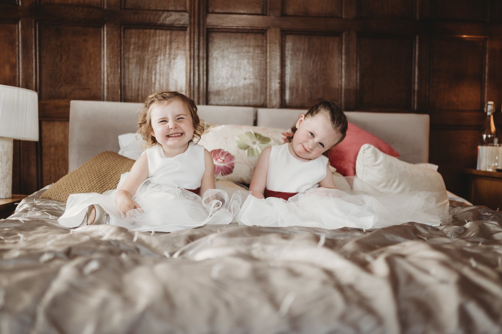 Young children smiling in bed as they wait for the wedding to begin