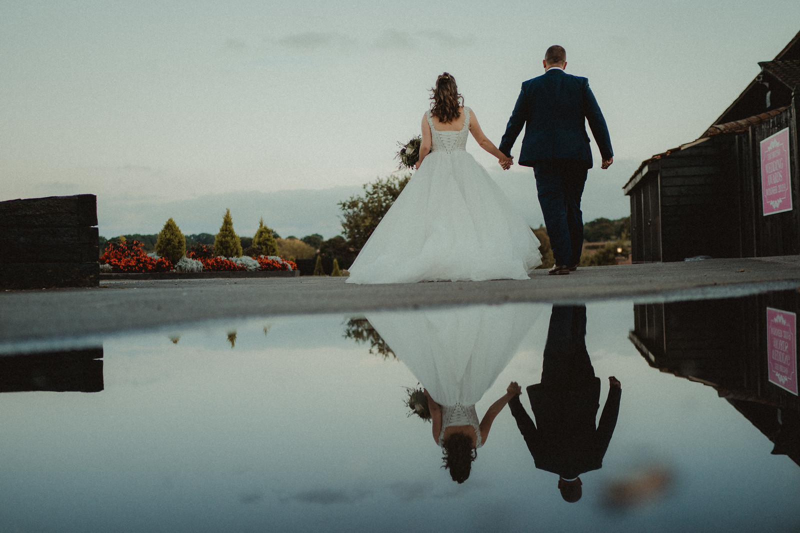 Bride and grooms reflection of love in a puddle - Wedding Photography