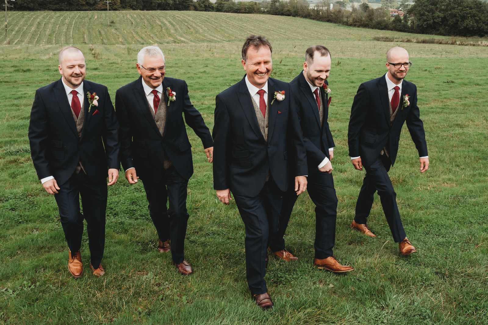 Groom and groomsmen smile as they walk to the venue