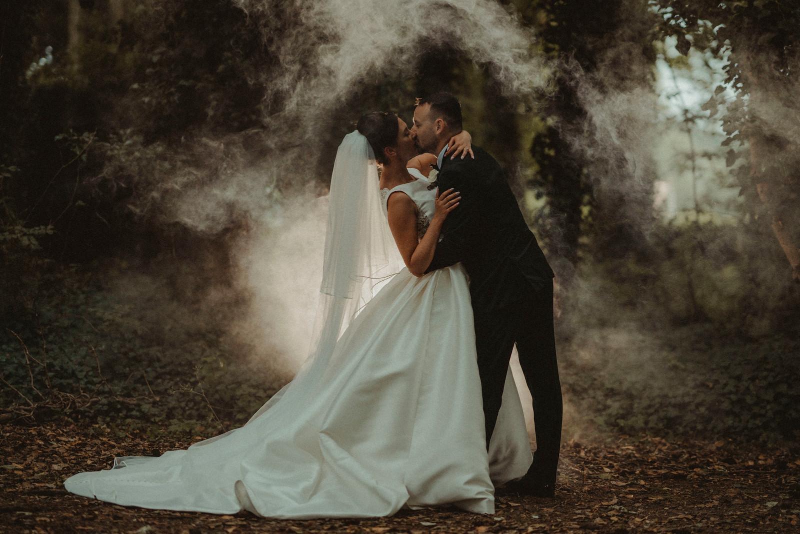 Bride and groom kiss with smoke around them| Wedding Photographer and Videographer