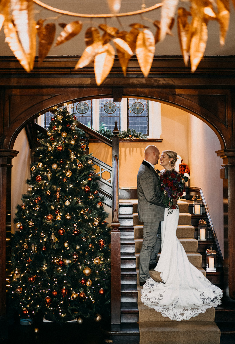 Bride and groom look at each other standing next to a Christmas Tree